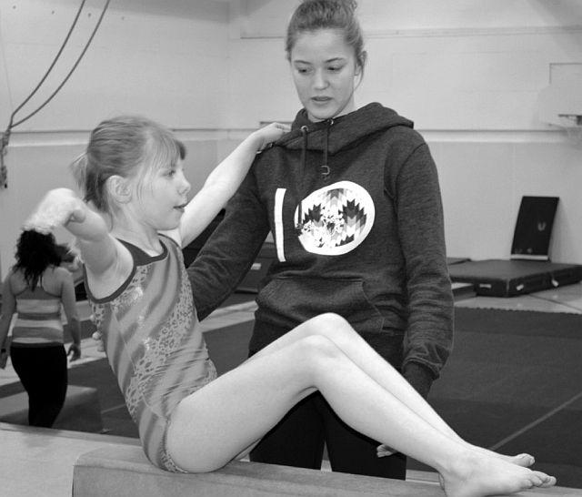 Junior coach Shanele Morin works with Sara Gordon on the balance beam.