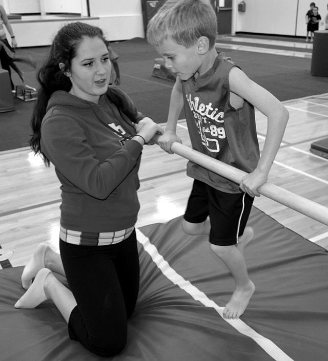 Junior coach Chantal Laflamme works with Reid Turnquist on the uneven bars.