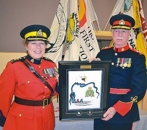 RCMP K Division Chief Supt. Brenda Lucki, left, presents special gift to Lakesshore Regioal Police Service accepted by Dale Cox, Chief of Police.