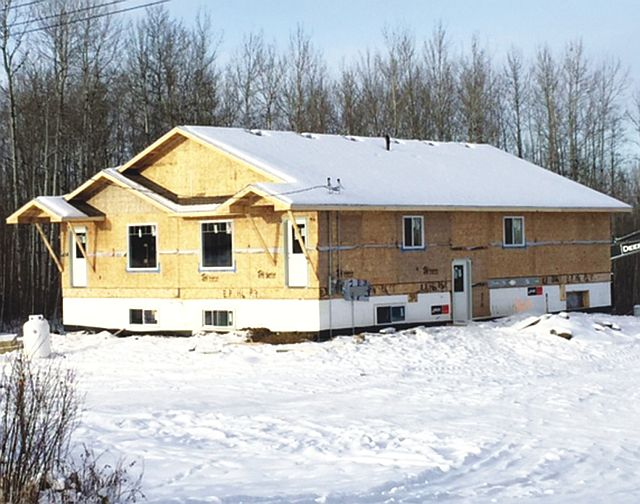 Another style of bungalow duplex at East Prairie Metis Settlement with the exterior shell complete.