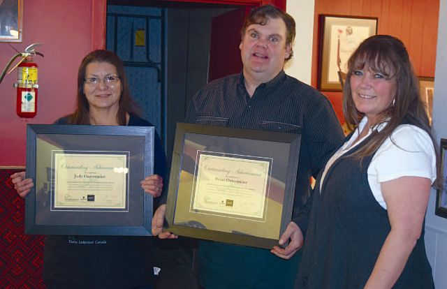 Left-right are Judy Ostermeier, Bryan Ostermeier with their 15-year service awards and presenter Tammy Kaleta. Not shown is the Ostermeiers' son, Max Ostermeier, who is a 10-year recipient.
