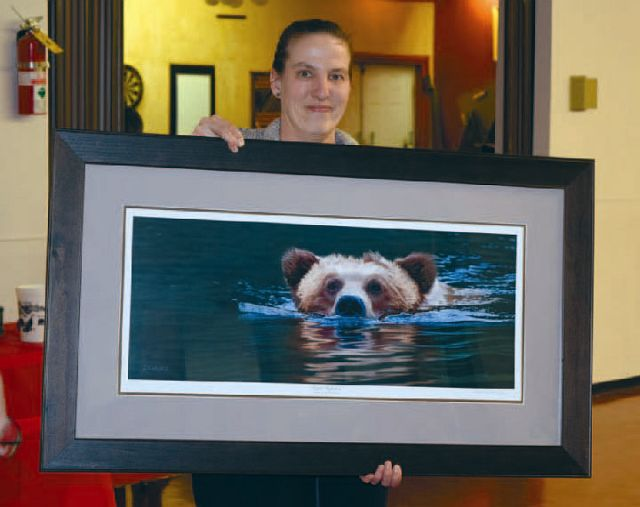 volunteer Joanne Corbiere with a live auction item. It was one of several prints up for auction.