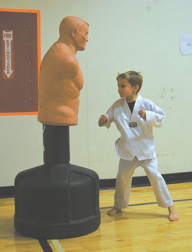 Reid Turnquist, 6, sets up a punch Body Opponent Bag (BOB).
