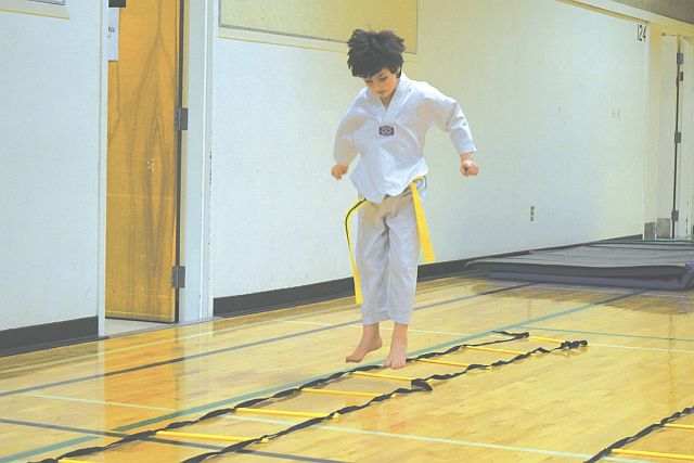 In the photo at left, Hayden Labrecque does a hopscotch-like move through the jacob's ladder, which is a work drill.
