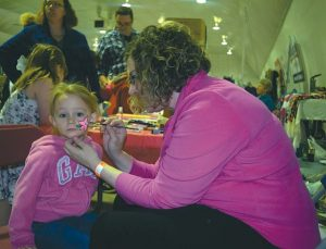 Sadie Cox, 2, gets her face painted by Laura Rutherford at the home-based business and crafters show in the curling rink.
