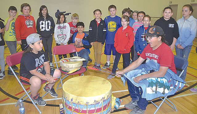 Wapastim Isadore-Bellerose, left, and brother Mikisiw Isadore-Bellerose, of Driftpile, beat the drums and sing as students at High Prairie Elementary School stand and listen during Aboriginal Day June 2.