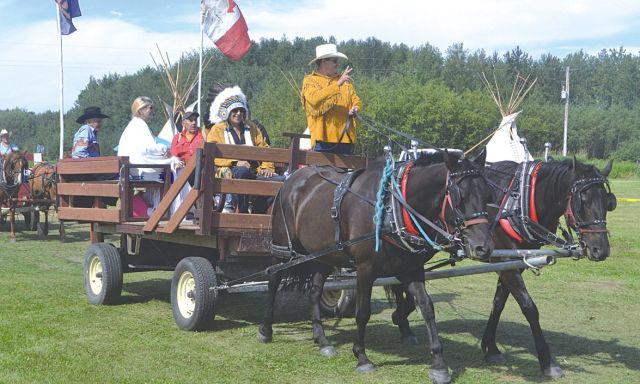 Sucker Creek Chief Jim Badger sits in a wagon as the wagon trades parades in council and elders before the Grand Entry on Saturday afternoon