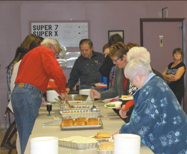 Those who attended the art show silent auction preparing to enjoy supper before results of the auction are announced.
