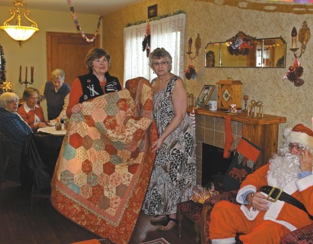 Jen Futter with Colleen Greer (right) holding the quilt Greer donated to Heritage House.