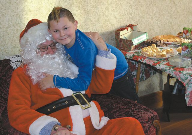 "A child greeting Santa at Heritage House ""Christmas in November"" event."