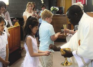 Students receive the sacraments at a special Mass at St. John the Baptist Cathedral